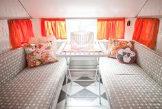 This 1960 Aristocrat LoLiner became a glam space fit for a movie star after a massive renovation by photographer Michelle Sullivan. Silver gray pairs with white in the diamond-pattern vinyl flooring, the shimmering wallpaper, and the geometric slipcovers, while pops of orange and pink take center stage in the fun curtains and throw pillows. See more at Michelle Sullivan Photography.   - CountryLiving.com