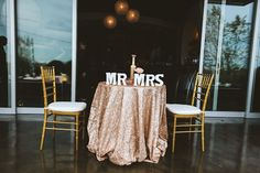 Sparkling gold tablecloth with Mr and Mrs table signs, photo by Ulmer Studios | junebugweddings.com