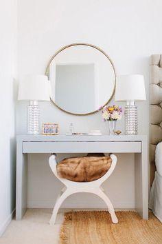 Penteadeira com espelho redondo e poltrona com assento de pelo.  #designdeinteriores