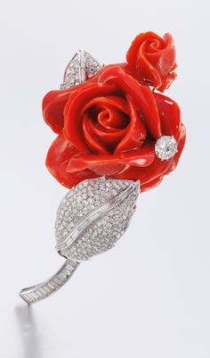 CORAL AND DIAMOND BROOCH, DESIGNED BY GINA LOLLOBRIGIDA, 1970S Designed as a carved coral rose decorated with a brilliant-cut diamond, the leaves and stem pavé-set with single-cut and baguette diamonds.