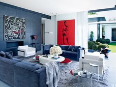 In the Florida home of baseball star Alex Rodriguez, the living room's blackened-steel panels make a rugged backdrop for a Keith Haring painting above a Spark Modern Fires fireplace and a Gérard Van Kal Mon sculpture from Holly Hunt; to the right is an Andy Warhol portrait of Jean-Michel Basquiat.