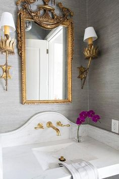 Gorgeous powder room features walls clad in gray grasscloth lined with an Alabama White marble top vanity and sink paired with a curved marble backsplash lined with a gold faucet under a gilt mirror illuminated by French brass wall sconces.