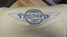"Triumph logo  ""World Class Motorcycles"" ""Since 1902""  Colors? Wing details?  Circle is supposed to look like a tire?"