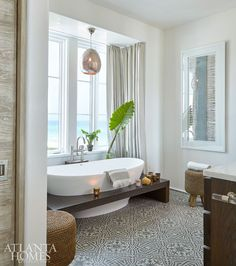 One of the best views in the house is from the guest bathroom. Mayers opened up the bathtub window, as well as the wall above the vanity, so those views could be enjoyed from the adjoining bedroom. Patterned tiles from the Cement Tile Shop fill the oasis.