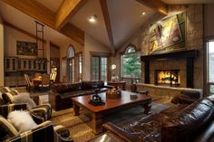 Another contemporary formal living room with deep, rich brown leather sofas paired with two striped armchairs and fluffy accent pillows in white. The fireplace has an ornate iron screen with ivy pieces wrapping around the sides. The wooden mantle is painted black.