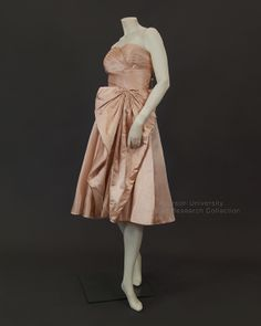 Pink silk satin strapless dress with full skirt and net lining. Bodice is boned and lined. Skirt is draped into petal shape. Large fabric bow on left hip, c.1950s. Label: Made in Italy for Creeds. FRC2013.99.005