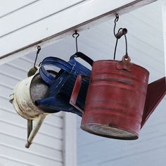 Hang rustic red, white, and blue watering cans for a fun outdoor decoration. Install screw eyes to hang the cans from sturdy hooks./