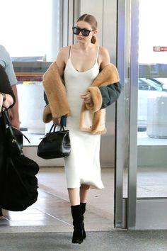 Gigi Hadid in a white slip dress, shearling jacket, Versace tote and Stuart Weitzman black velvet boots.