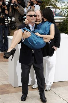 """Alec Baldwin sure made lifting his wife look easy at a photo op during the 2013 Cannes Film Festival. (Not.) The """"30 Rock"""" star looked ready to pop a blood vessel while showing off his upper body strength for the cameras.Like us on Facebook?"""