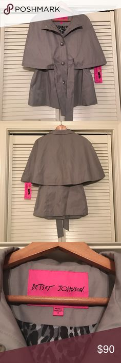 Betsey Johnson Belted Rain Cape With Luxe Buttons Rain or shine, maintain a chic attitude with this lightweight jacket. An adjustable sash cinches the waist, highlighting natural curves beneath flowy cape sleeves. Under the cape, the main body of the coat is sleeveless. NWT, never worn. Betsey Johnson Jackets & Coats Capes