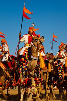 Men wearing ceremonial clothing and riding colourfully decorated camels during the annual Jaisalmer Desert Festival, a showcase of Rajasthani folk culture and arts