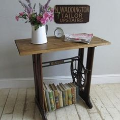 An old singer treadle sewing machine base with Singer on the cross stretcher and foot treadle, the sides are wooden. The base has had a pine top added to make a quirky side table for use around the home.