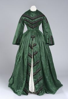 "1855 dressing gown: Green satin dressing gown with floral print; trimmed in 1/2"" black silk ribbon with 4 stripes of black velvet on front; simple round collar; 14 hook fasteners down front to waist then skirt is open to the floor; 3/4 length sleeves trimmed with 3 black ribbons at shoulder and 5 black ribbons at wrist; bodice lined with tan glazed linen and 4 stays; skirt lined in pink/white printed cotton;  Worn by donor's grandmother Jane Wadham Stevens"