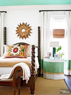 Traditional-style furniture mixes with eclectic accessories in this bright bedroom. A sunburst mirror hangs above the charming four-poster, creating a stunning focal point that echoes lines featured in the printed pillow shams. A skirted nightstand lends a tailored look and ties in with the window draperies and the bold turquoise hue of the ceiling. Draperies hung several inches above the window trim draw the eye upward to further call attention to the room's soaring height. What we love: Hi...