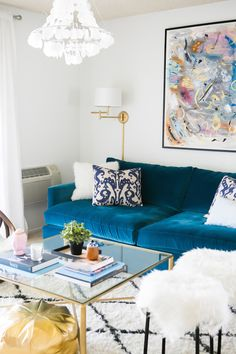 Katherine Vo - Fabulous living room features colorful abstract art lit by a Home Decorators Pivoting Swing Arm Pin Up Lamp over a peacock blue velvet sofa accented with fluffy white pillows and purple ikat pillows. A gold x based coffee table stands in front of the sofa with a metallic gold pouf below and a pair of Ikea Fur Stools to the right atop a Beni Ourain style rug lit by a capiz shell chandelier.