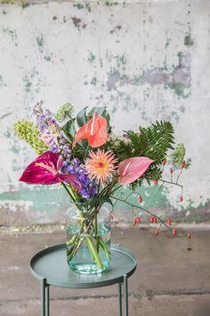 Een kleurrijk anthurium boeket: in dit artikel delen we 5 voorbeelden, om je de veelzijdigheid van deze bloem te laten zien en je inspiratie te bieden om zelf aan de slag te gaan. De exotische bloem komt niet alleen in de meest uiteenlopende kleuren, de vormen variëren ook van hart-, naar tulp- en lintvormig. Dat maakt de anthurium snijbloem ideaal om te verwerken in een boeket!   anthurium boeket - boeket met anthurium - anthurium arrangement - anthurium bloemschikken - anthurium bloemstuk Glass Vase, Interior, Flowers, Plants, Home Decor, Tulips, Decoration Home, Indoor, Room Decor