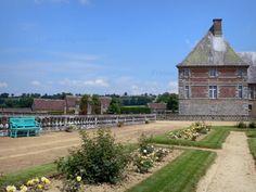 Château de Carrouges: Parterres fleuris (rosiers en fleurs, roses) du jardin et façade du château - France-Voyage.com