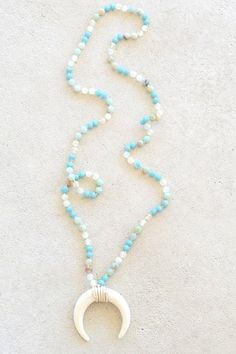 Inspired by the beautiful crystal blue waters, this statement necklace is a one-of-a-kind accessory your friends with go crazy for! Shades of green and blue beads hold the beautiful double tusk pendan