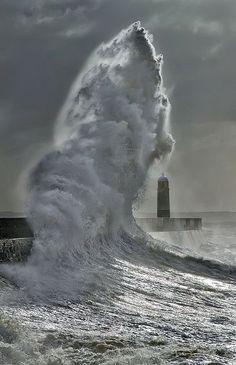A giant wave crashes against Porthcawl Pier in South Wales during a winter storm.