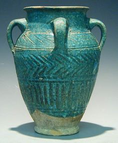 : A Turquoise glazed pottery jar with four handles, Iran, 13th century A.D. Incised design consisting of a band of diagonal lines, chevron...