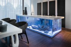 Dutch interior designer Robert Kolenik has designed a visually stunning kitchen counter that features a aquarium built inside it. The island's entire base is a large glass tank that's topped with a cl...