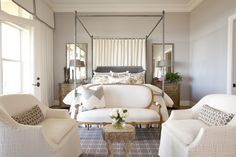 bedrooms - gray walls wall French doors transom windows white cornice boards gray trim canopy bed gray velvet headboard wood nightstands gold French settee white gray chevron pillow white textured chairs gray lumbar pillows gray rug