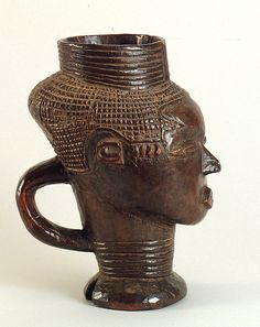 "Democratic Republic of the Congo; Kuba peoples Palm wine cup Wood H. 20.6 cm (8 1/8"") The University of Iowa Museum of Art, The Stanley Collection, X1986.183 This cup bears the distinctive Kuba hairstyle, which is frequently depicted on Kuba objects (The University of Iowa Museum of Art, The Stanley Collection, X1986.185, X1986.304)."
