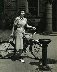 """Woman on a bicycle modeling a dress, designed by a student at Pratt Institute."""
