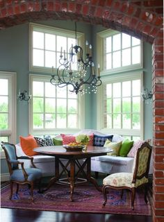 Awesome Banquette Style Dining Space with beautiful round wood table and various seating options, along with very pretty chandelier and exposed brick, and amazing windows that let in tons of natural light.  {{{LOVE}}} this space!!
