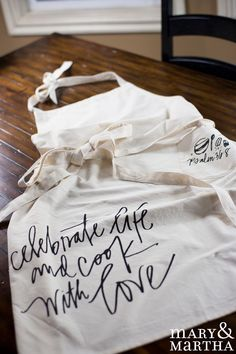 Homes everywhere love our Cook With Love apron with handlettering by @lindsay_letters. Make it personal by having your kiddos put their handprints on the apron using paint!