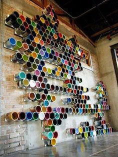 Parede decorada com latas de tinta coloridas vazias.