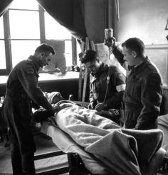 Canadian medics Sgt. T.F. McFeat, Cpt. Earl Bourbonnais and Pvt. J. Viner of the 23rd Field Ambulance, assigned to the 9th Infantry Brigade of the 3rd Canadian Infantry Division, administer blood plasma to a wounded comrade during the Battle of Normandy. 27 June 1944.
