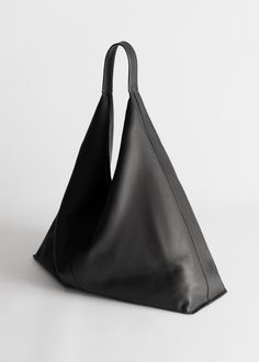 Slouchy smooth leather tote bag with a sculptural, triangular silhouette and an ergonomic strap for carrying by hand or over the shoulder. DESIGNED IN STOCKHOLM Smooth Leather Tote Bag in black by & Other Stories. #ad #affiliatelink