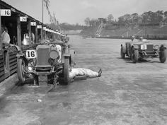 As another car races past, a mechanic lies with his legs on the track as he works on a Lea-Francis cc that was retired from the race due to engine issues at the Brooklands JCC Double Twelve. Note the wooden pit lane huts Vintage Sports Cars, Vintage Race Car, Vintage Auto, Classic Motors, Classic Cars, Old Race Cars, F1 Racing, Modified Cars, Car And Driver