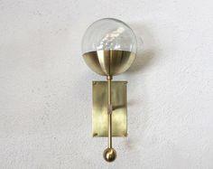 E S T  Modelo es pantalla de vidrio claro y bronce de cepillado a mano. Esta lámpara solo bulbo puede ser colgado en cualquier dirección - hacia arriba o hacia abajo e incluso dio vuelta diagonalmente. Latón crudo rectangular cubierta con una cortina de globo de cristal claro y mano vuelta bola de cobre amarillo de la pared. Es impresionante por un pasillo, sobre un espejo de baño, imponente a cada lado de la cama, o incluso en el techo.  DIMENSIONES • 15 L x 7 proyección de la pared x 6,5…