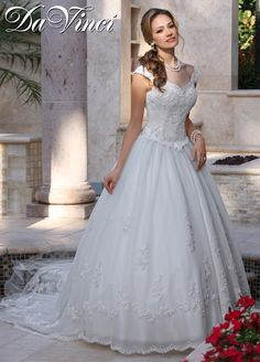 This gown has a scalloped sweetheart neckline with off the shoulder straps. The tulle skirt offers pearl-like beads and scattered lace appliques.