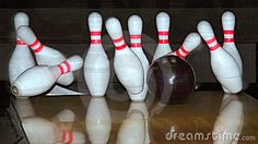 Closeup of a bowling ball and falling pins.