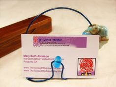Handcrafted Business Card Holder, Blue Wire Sculpture with Chunky Porcelain Flower, Miniature Stand for Keepsake Photo, Memorable Note Created free-form with color-coated blue copper wire, this handmade perch is just the ticket for your signature business cards.  For a little pizzazz, I've added a transparent blue glass bead front and center, and a fun chunky porcelain flower in white with blue and dark honey marbling.