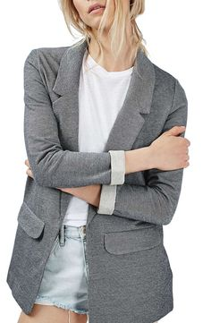 A notched lapel dips down to the button-free front of this two-tone cotton boyfriend-style blazer tailored with two flap pockets at the hips.