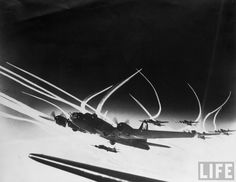 Squadron of B-17 bombers of the 13th Wing, 390th Bomb Group framed by vapor trails from their fighter escorts.  Date taken 1943