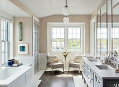 The master bath boasts pendant lights by Rejuvenation, a Ralph Lauren Home sconce, and a pair of vintage French chairs from Aero; the sink fittings are by Waterworks.