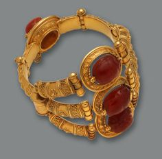 An archaeological [Egyptian] revival eighteen karat gold and carnelian scarab bangle bracelet, Castellani, circa 1860 -   the hinged bangle designed as three articulated arched panels, each centering a rotating carved carnelian scarab, adjoined by a single arch and scarab clasp of similar design, detailed throughout with intricate applied wiretwist and granulation embellishment; unsigned, attributed to Castellani; diameter: 2 1/2in.