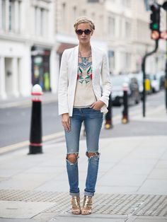 Poppy Delevingne in a chic white jacket, paired with an embroidered blouse, ripped jeans, and sparkly heels
