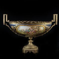 Lot #135: Sevres Bronze & Porcelain Centerpiece DESCRIPTION: Large Sevres porcelain and gilded bronze centerpiece, the top half features a cobalt blue bowl decorated with gilt ornate overlay, hand painted courting couples on one side and a floral motif on the other. The porcelain bowl is sustained by a gilded bronze floral frame finished with squared handles. In excellent condition  CIRCA: 19th Ct. ORIGIN: France DIMENSIONS: L: 21.5″ H: 15″ W: 7″