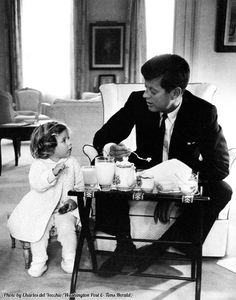 President Kennedy has a breakfast conference with his daughter Caroline in the residence area of the White House in 1961.