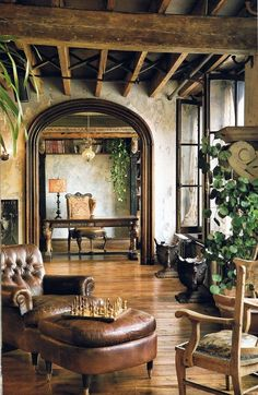 interesting mix - rustic ceiling beams with iron supports, stucco walls, wood trimmed arched doorways, metal (black steel/iron) windows, rustic wood floors - makes this a very special space