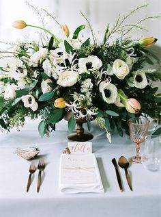 Flowerup created this elegant, neutral-colored centerpiece using anemones, tulips, ranunculi, and eucalyptus. | Photo by Peaches & Mint