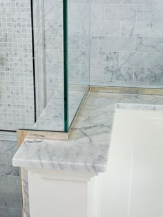 A marble ledge on this shower provides a handy place to rest toiletries and protects the wood paneling from splashes.