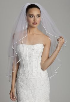 This simply beautiful ribbon edge veil is the ideal choice for a bride that wants to let her dress and beauty do all of the talking. The double layer fingertip veil creates delicate volume but acts as an accent piece to enhance your stunning wedding day look. The sweet ribbon will complement dresses like a strapless ballgown wedding dress, strapless satin wedding dress with bow sash, or a beaded lace wedding dress with scoop neck and you will be the most striking bride there is!