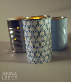 Tin cans are a fantastic way to add candle light to your event. They are truly a blank canvas and can can be decorated with many techniques. I chose to drill holes, cover with patterned paper, and paint these three cans. Once you've taken care of the outside, drop a votive in and light!